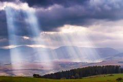 Fasci di luce solare sopra le nuvole in montagne Raggi in cielo nuvoloso immagine stock libera da diritti
