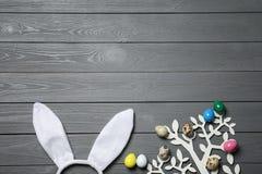 Fascia delle orecchie del coniglietto di pasqua ed albero decorativo con le uova variopinte su fondo di legno, disposizione piana immagine stock