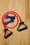 Fascia rossa di resistenza e pesi blu sul pavimento di ginnastica Immagini Stock