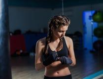 Fasciatura d'uso della mano della giovane del combattente ragazza del pugile durante l'addestramento i Fotografie Stock Libere da Diritti