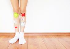Fasciature variopinte sulla gamba dei childs Fotografie Stock Libere da Diritti