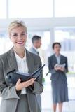 Fascicoli aziendali ed esame sorridenti della donna di affari della macchina fotografica Fotografia Stock Libera da Diritti