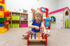 Fascinated маленькая девочка играя с деревянным молотком в kindergarte стоковое фото rf