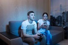 Fascinated молодой человек играя видеоигру пока его th wifesurf стоковая фотография