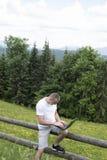 Fascinated человек сидя на деревянной загородке и работах за ноутбуком около полей и сосновых лесов Вертикальная рамка стоковая фотография