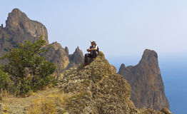 Fascinated by the beauty of the mountains of an ancient volcano Kara-Dag female tourist. Crimea stock photo