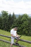 Fascinated man sitting on a wooden fence and works behind the laptop near the fields and pine forests. Vertical frame.  stock photography