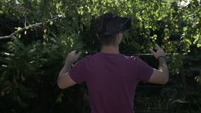 Fascinated teenager with VR set exploring green recreational area testing virtual reality technology in slow motion -. Fascinated teenager with VR set exploring stock video footage