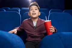 Fascinated teenager watching movie attentively in cinema. Shocked, fascinated boy sitting in movie theatre, looking at screen attentively with opened mouth stock photo