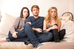 Fascinated teenagers sitting watching television Stock Photo