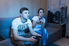 Fascinated young man playing a video game at home with his girlf Royalty Free Stock Image