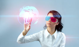 Fascinating brunette wearing 3d anaglyph stereo gl. Operating futuristic 3d interface. Touching three-dimensional globe. One of a series Stock Photo