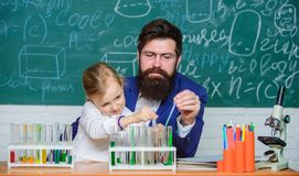 Fascinating chemistry lesson. Man bearded teacher and pupil with test tubes in classroom. Private lesson. School. Chemistry experiment. Explaining chemistry to royalty free stock image