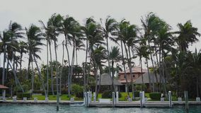 Fascinating mansion among beautiful palm trees on the shore with private dock for boats on sunny isles beach,miami. Magnificent big house of rich people between stock footage