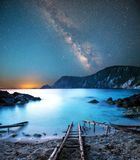 Fascinating mystical magical landscape with a deach and boat racks at night in the light of the Milky Way stars.  stock images