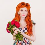 Fascinating smile on face. Valentines day concept. Beautiful stylish attire. Happy redhead model with hairstyle with bouquet. Of roses isolated on gray royalty free stock photos