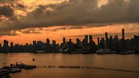 Fascinating steady time lapse panorama of gray rain cloud moving in evening orange sunset sky over New York city skyline. Fascinating steady time lapse panorama stock video footage