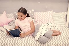 Fascinating story. Girl child lay bed with pillows read book. Kid prepare to go to bed. Time for evening fascinating. Story. Girl kid long hair cute pajamas stock image