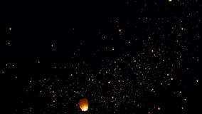 Fascinating view on bright oarnge lighted candle chinese paper lanterns floating slowly in dark black night festival sky. Fascinating view on bright oarnge stock footage