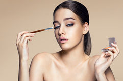 Fascinating young girl with brush for eyeshadow. Stock Photography