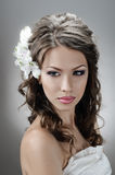 Fascination bride. Portrait of beautiful bride with flowers in hair on grey Royalty Free Stock Photos