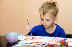 Fascination with drawing. The boy draws a table in the studio Stock Images