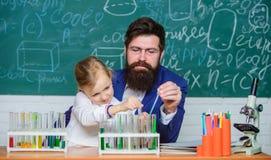 Fascinera kemikurs L?rare och elev f?r man sk?ggig med provr?r i klassrum Privat kurs skola royaltyfri bild