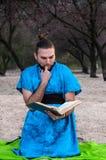Fascinerad stilig skäggig man i blå kimono med fingret i munnen som sitter med boken arkivfoto