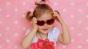 fascino Modo bellezza Un fashionista sveglio del bambino gioca una signora reale Fondo rosa La bella bambina veste il rosso archivi video