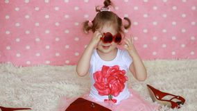 fascino Modo Fashionista La bambina sveglia veste gli occhiali da sole rossi sotto forma dei cuori Fondo rosa divertente video d archivio