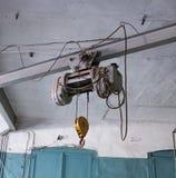 Fascio della gru con il motore ed il gancio, appendenti sulle corde d'acciaio, gru industriale della sospensione fotografia stock libera da diritti