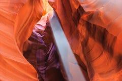 Fascio di raggio del sole e polvere fra le pareti variopinte dell'arenaria del canyon superiore e più basso dell'antilope vicino  Immagini Stock