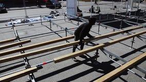Fase della via di configurazione dei lavoratori per l'evento costruzione L'uomo presenta i bordi di legno stock footage