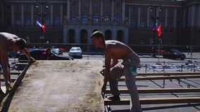 Fase della via di configurazione dei lavoratori per l'evento di estate Presenti i bordi di legno sunny stock footage