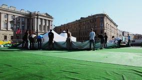 Fase di configurazione degli uomini per l'evento sulla via Il gruppo di lavoratori tiene la tenda verde enorme Sun video d archivio