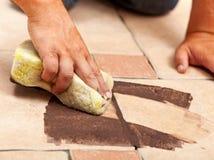 Fasen van het installeren van ceramische vloer die - het gezamenlijke materiaal betegelen Royalty-vrije Stock Afbeelding