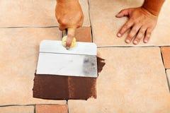 Fasen van het leggen van ceramische vloertegels - pas het gezamenlijke materiaal toe Stock Afbeelding