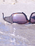 Fashinable sunglasses on the sand Royalty Free Stock Photo