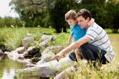 Fashing and Son Playing Near Lake Royalty Free Stock Photos