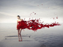 Fashion. Beautiful woman on a pier with red dress melting in red paint Stock Images
