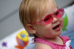 Fashion. A portrait of an adorable baby girl wearing pink sunglasses royalty free stock images