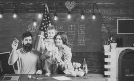 Fashion accessories. American family at desk with son making paper planes. Homeschooling concept. Kid with parents in. Classroom with usa flag, chalkboard on Royalty Free Stock Images
