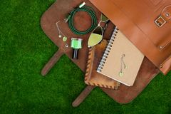 Fashion accessories - bag, note pad, purse, nail polish essentials on the grass. Female fashion accessories - bag, note pad, purse, nail polish essentials on the Stock Photography