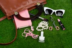 Fashion accessories - bag, note pad, sunglasses, headphones, lipstick and other essentials on the grass. Female fashion accessories - bag, note pad, sunglasses Stock Photos