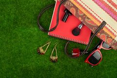 Fashion accessories - bag, note pad, sunglasses and other essentials on the grass. Female fashion accessories - bag, note pad, sunglasses and other essentials on Stock Photo