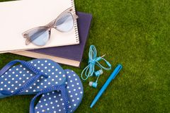 fashion accessories - flip flops, book, note pad, pen, headphones, note pad, sunglasses on the grass royalty free stock photos