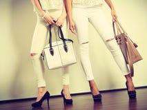 Two ladies holding handbags. Stock Photos