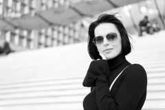 Fashion and accessory. Woman in sunglasses on stairs. Ambition, challenge, success concept. Girl with brunette hair in black clothes. Look, beauty, style stock photos