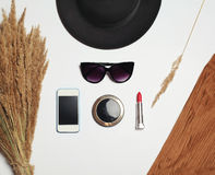 Fashion accessory, round black hat, sunglasses, screen smartphone, mirror and red lipstick on white background Royalty Free Stock Photos