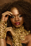 Fashion African or American woman with black curly hair, gold makeup and accessories posing holding hands near face Stock Image